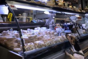 Cheese counter with dog looking on